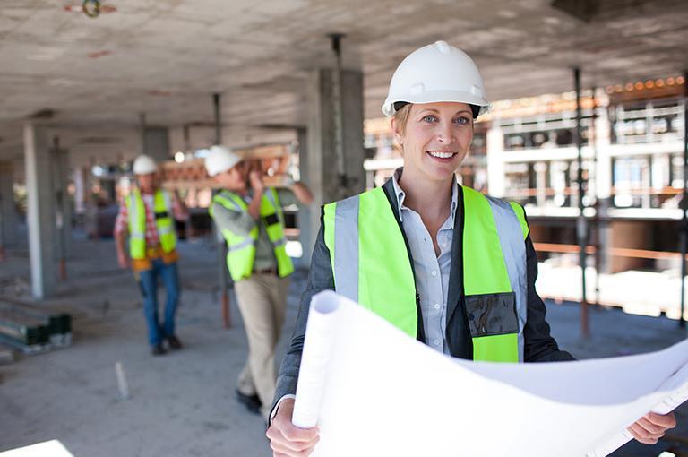 Architektka zplanem budowy natle pracowników niosących drabinę